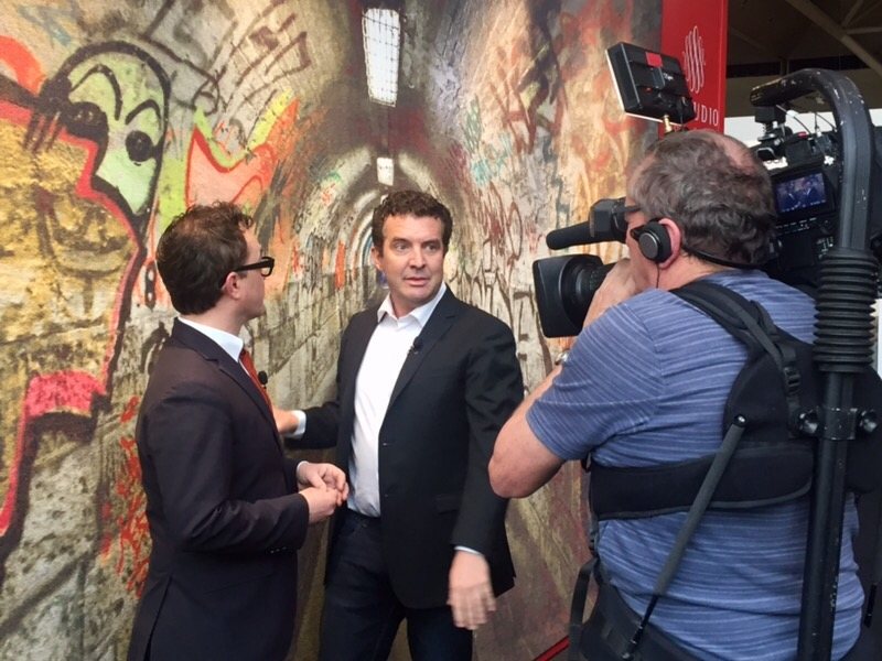 Image of Rick Mercer and Tommy Smythe on the Rick Mercer Report do an IDS roundup. The segment showcases Rick and Tommy in front of our famous Tunnel carpet on display at IDS. W STUDIO is mentioned at the 12:50 mark.